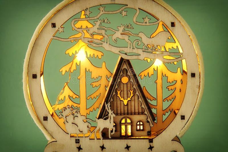 Imagen de la escena mágica de la Navidad del bosque, de la choza y de Papá Noel de madera del pino sobre trineo con los ciervos imágenes de archivo libres de regalías