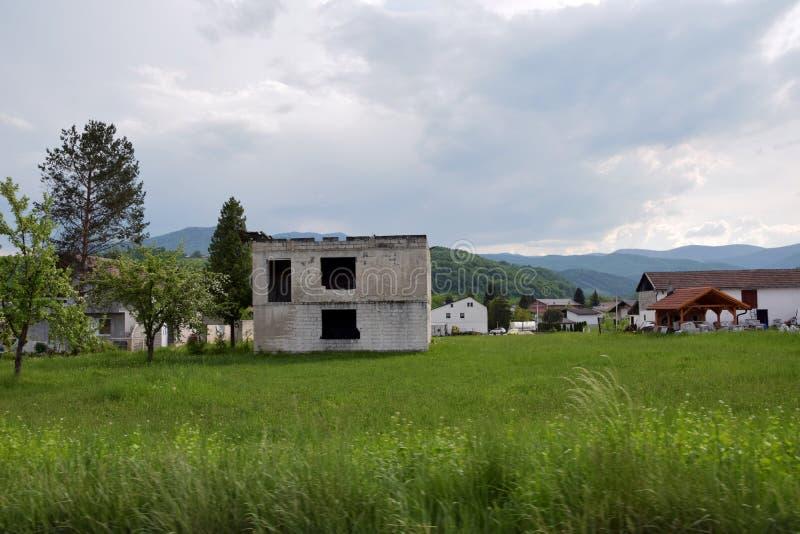 Imagen de la estructura inacabada devastada de la casa en área del pueblo rural foto de archivo