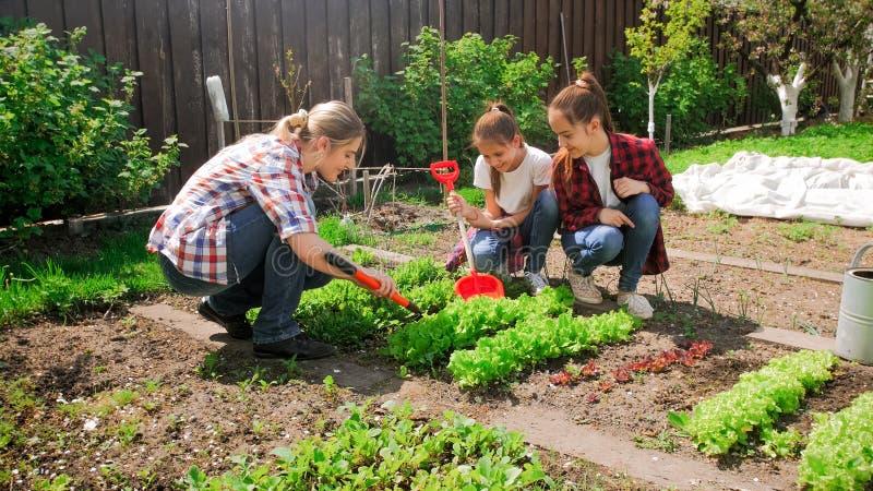 Imagen de la familia con los niños que trabajan en jardín fotos de archivo