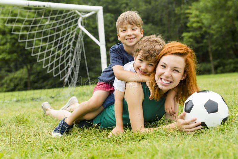 Imagen de la familia, de la madre y del hijo jugando la bola en el parque fotografía de archivo