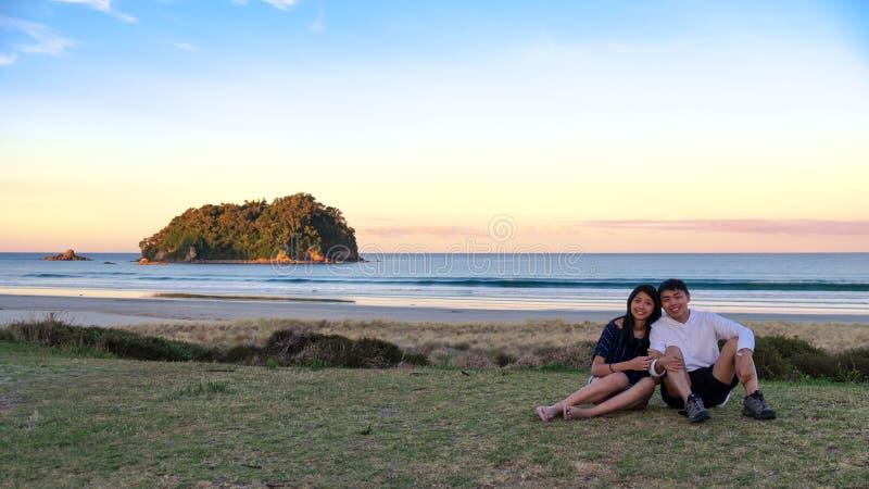 Imagen de la forma de vida de los pares asiáticos jovenes que se sientan en campo de hierba a lo largo de la costa con el cielo d imagen de archivo