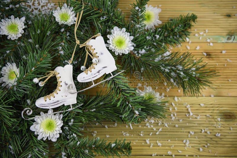 Imagen de la fotografía de la Navidad con la decoración de las botas de las ramas de árbol y del patinaje de hielo y flores blanc imagen de archivo