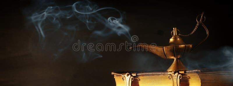 Imagen de la lámpara de aladdin mágica y de libros viejos Lámpara de deseos imágenes de archivo libres de regalías