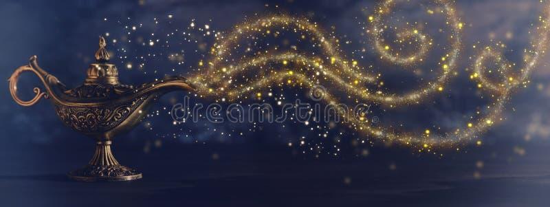 Imagen de la lámpara de aladdin misteriosa mágica con humo de la chispa del brillo sobre fondo negro Lámpara de deseos foto de archivo