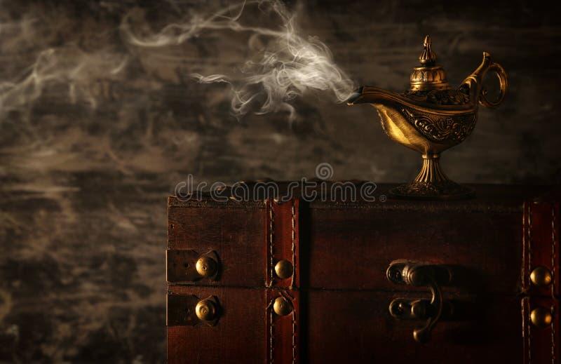 Imagen de la lámpara de aladdin misteriosa mágica con humo sobre fondo negro Lámpara de deseos fotografía de archivo