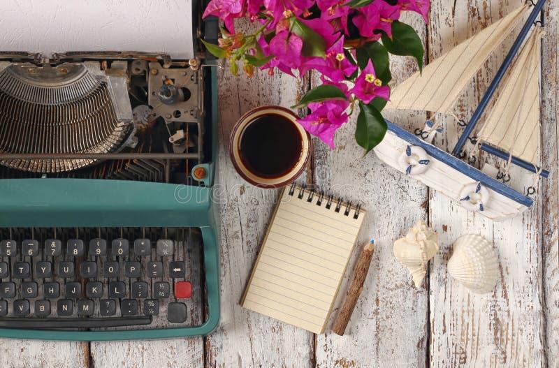 Imagen de la máquina de escribir del vintage, del cuaderno en blanco, de la taza de café y del velero viejo en la tabla de madera imagen de archivo