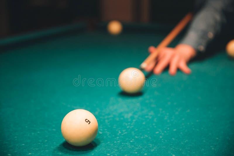Imagen de la mano del hombre que lleva a cabo señal del billar y que apunta a la bola breal él juega dentro en la cama de la tabl imagen de archivo libre de regalías