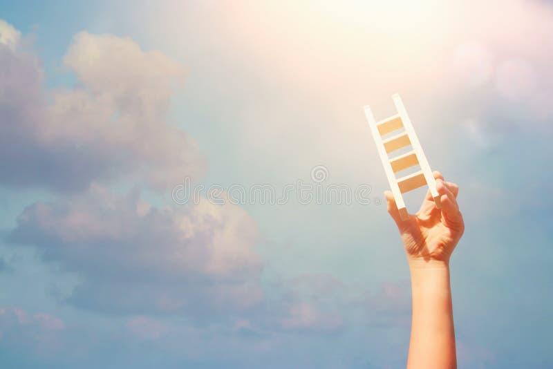 Imagen de la mano del niño que sostiene una escalera contra el cielo Educación y concepto del éxito fotografía de archivo libre de regalías