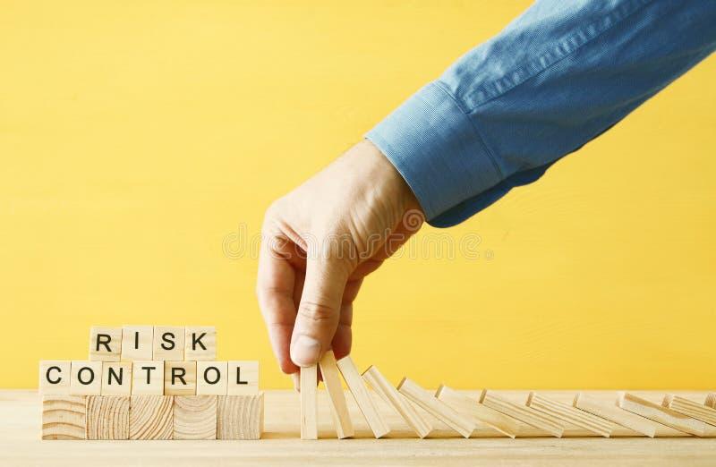 Imagen de la mano masculina que para el efecto de dominó ejecutivo y concepto de control del riesgo imagen de archivo libre de regalías