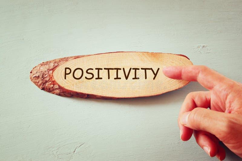 Imagen de la mano masculina que señala en la muestra de madera con la positividad de la palabra imágenes de archivo libres de regalías