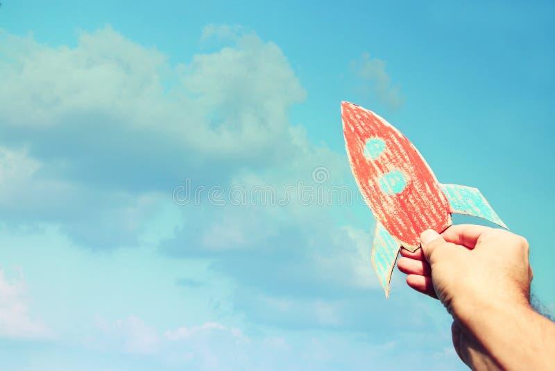 Imagen de la mano masculina que sostiene un cohete contra el cielo imaginación y concepto del éxito foto de archivo