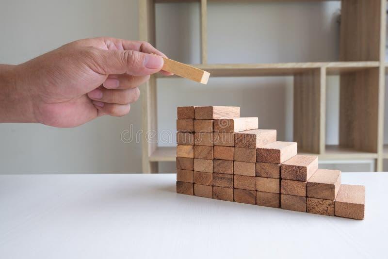 Imagen de la mano que lleva a cabo el juego de madera de los bloques a crecer del negocio Riesgo de plan de gestión y de la estra fotografía de archivo libre de regalías