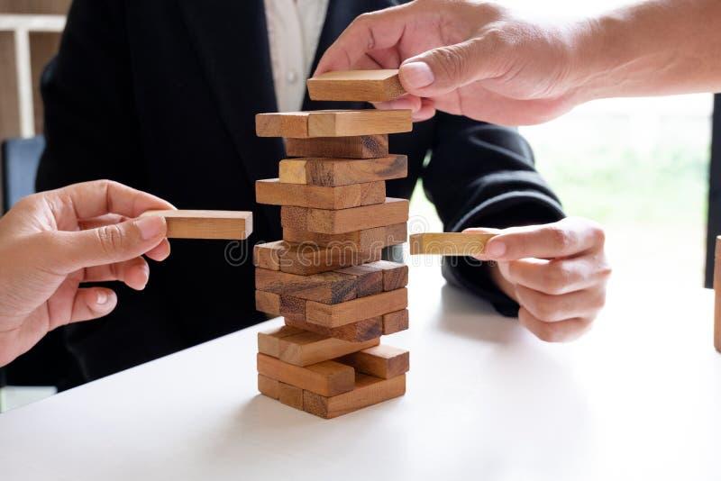 Imagen de la mano que lleva a cabo el juego de madera de los bloques a crecer del negocio Riesgo de plan de gestión y de la estra imagen de archivo libre de regalías