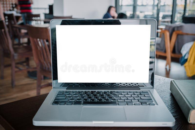 Imagen de la maqueta del ordenador portátil con la pantalla blanca en blanco en la tabla de madera foto de archivo libre de regalías