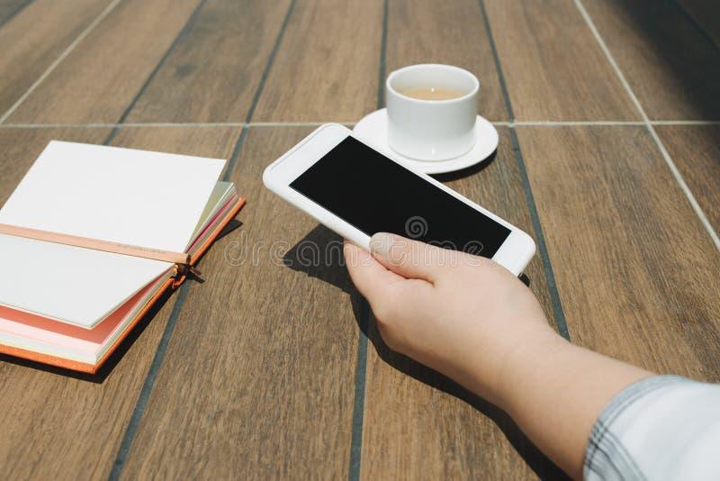 Imagen de la maqueta de las manos que sostienen el teléfono móvil blanco con la pantalla de escritorio negra del espacio en blanc fotografía de archivo