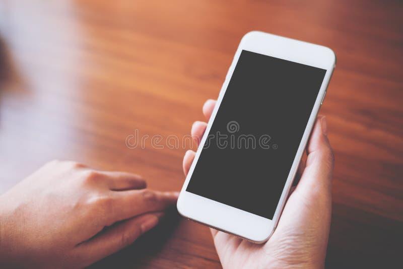 Imagen de la maqueta de las manos que sostienen el teléfono móvil blanco con la pantalla negra en blanco con la taza de café cali imágenes de archivo libres de regalías