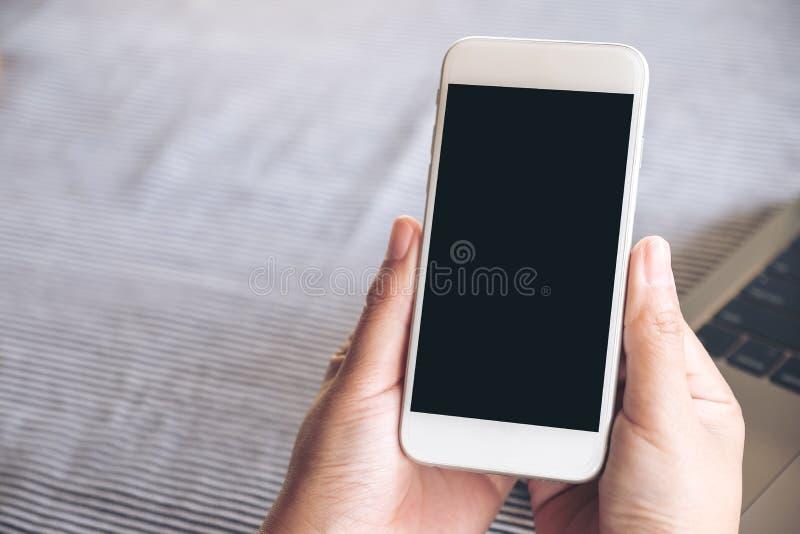 Imagen de la maqueta de las manos que sostienen el teléfono móvil blanco con la pantalla y el ordenador portátil de escritorio ne fotos de archivo libres de regalías