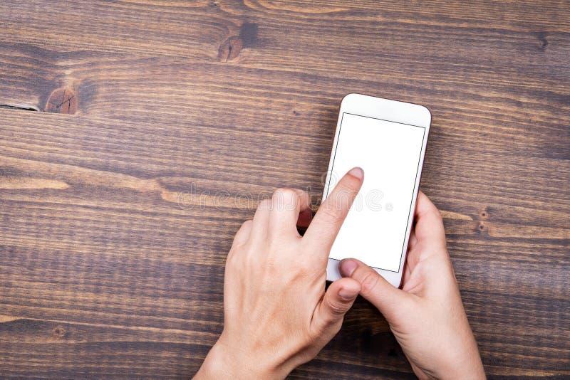 Imagen de la maqueta de las manos que sostienen el tel?fono m?vil blanco con la pantalla blanca en blanco fotos de archivo libres de regalías