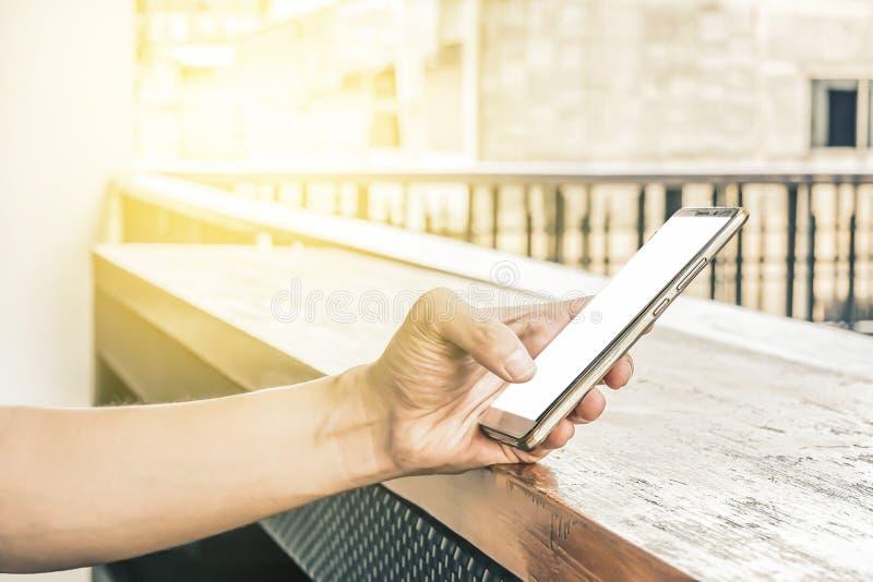 Imagen de la maqueta de la mano que sostiene el teléfono móvil con la pantalla blanca en blanco fotografía de archivo