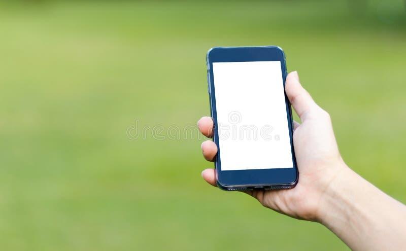 Imagen de la maqueta de la mano que sostiene el teléfono móvil negro con blanco en blanco fotos de archivo libres de regalías