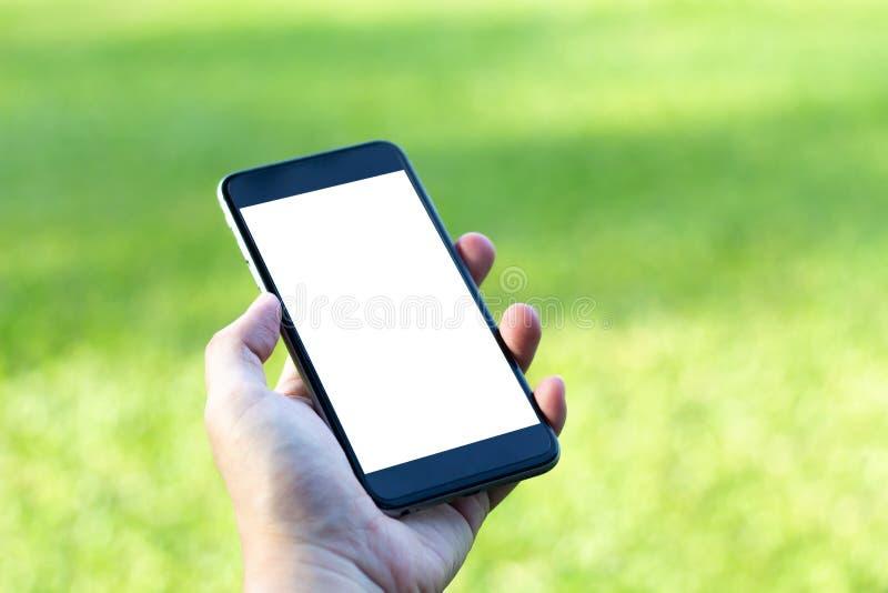 Imagen de la maqueta de la mano que sostiene el teléfono móvil negro con blanco en blanco foto de archivo libre de regalías