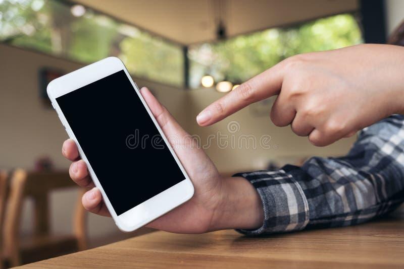 Imagen de la maqueta de la mano que sostiene y que señala el finger en el teléfono móvil blanco con la pantalla de escritorio neg foto de archivo
