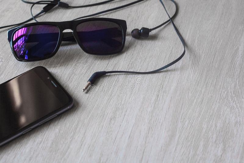 Imagen de la maqueta de la regla de los auriculares del caucho de l?piz del cuaderno de las gafas con el tel?fono m?vil negro y l foto de archivo