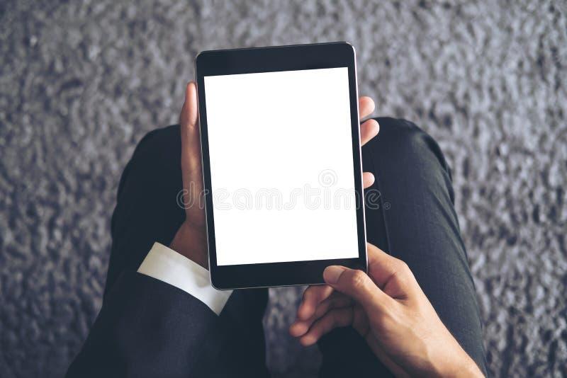 Imagen de la maqueta de un hombre de negocios que sienta y que sostiene la PC negra de la tableta con la pantalla blanca en blanc foto de archivo