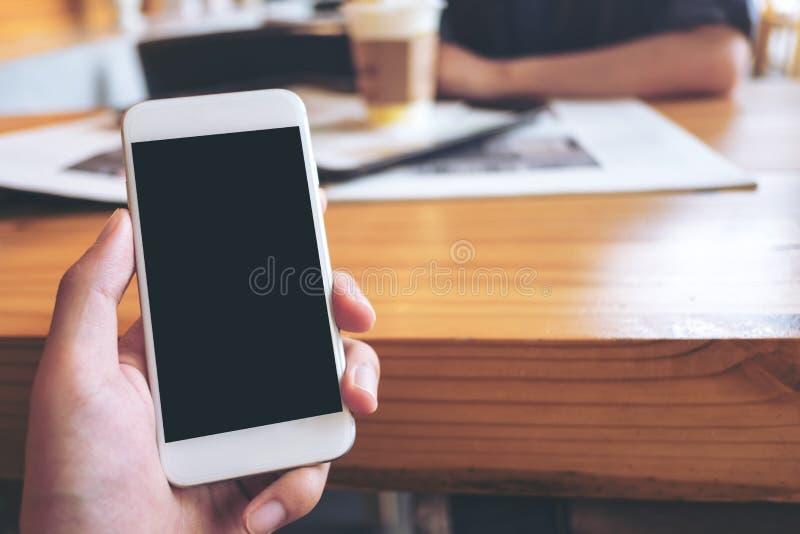Imagen de la maqueta de una mano del ` s del hombre que sostiene el teléfono móvil blanco con la pantalla negra en blanco en café imagen de archivo