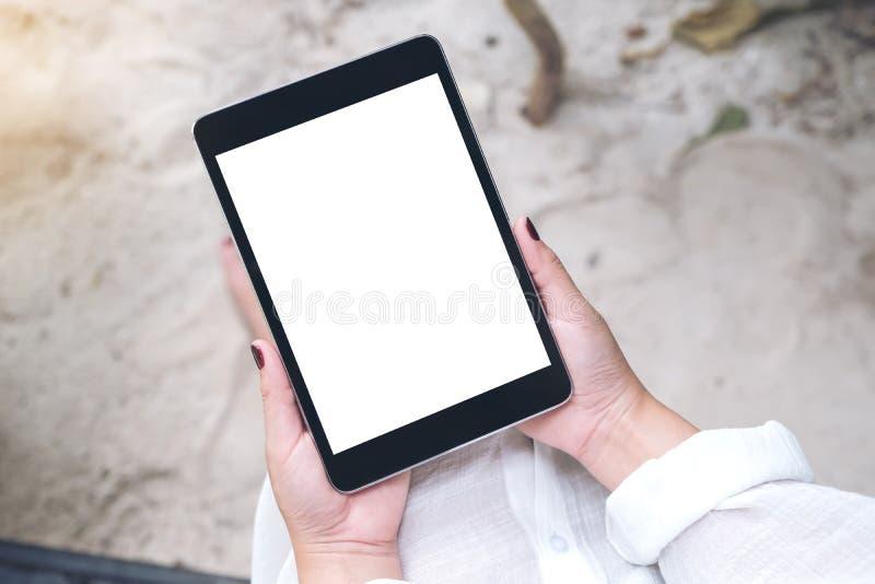 Imagen de la maqueta de una mano del ` s de la mujer que sostiene la PC negra de la tableta con la pantalla de escritorio blanca  foto de archivo libre de regalías