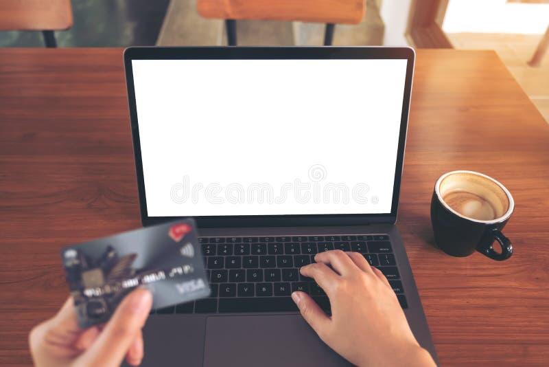 Imagen de la maqueta de una mano que sostiene tarjetas de crédito mientras que usa y mecanografía en el ordenador portátil con la imagen de archivo libre de regalías