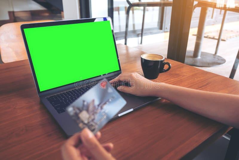 Imagen de la maqueta de una mano que sostiene tarjetas de crédito mientras que usa y mecanografía en el ordenador portátil con la fotos de archivo