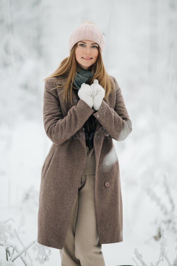 Imagen de la muchacha rubia feliz en sombrero en paseo en bosque del invierno fotos de archivo libres de regalías