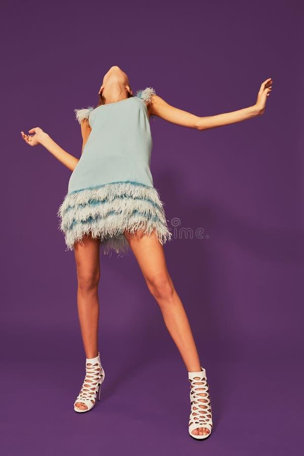 Imagen de la muchacha rubia joven bonita en el baile azul del vestido de cóctel en fondo púrpura en estudio fotos de archivo libres de regalías