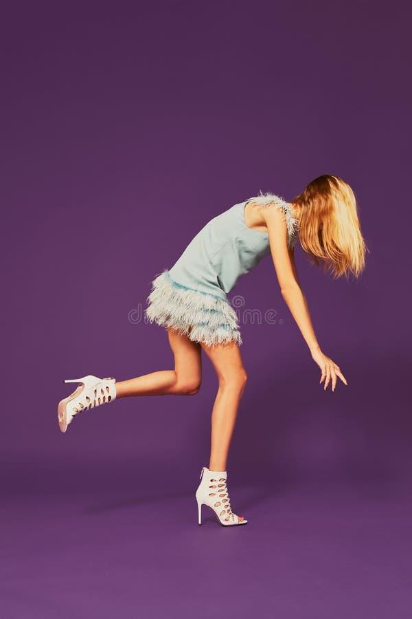 Imagen de la muchacha rubia joven bonita en el vestido de cóctel azul que intenta no caer foto de archivo libre de regalías