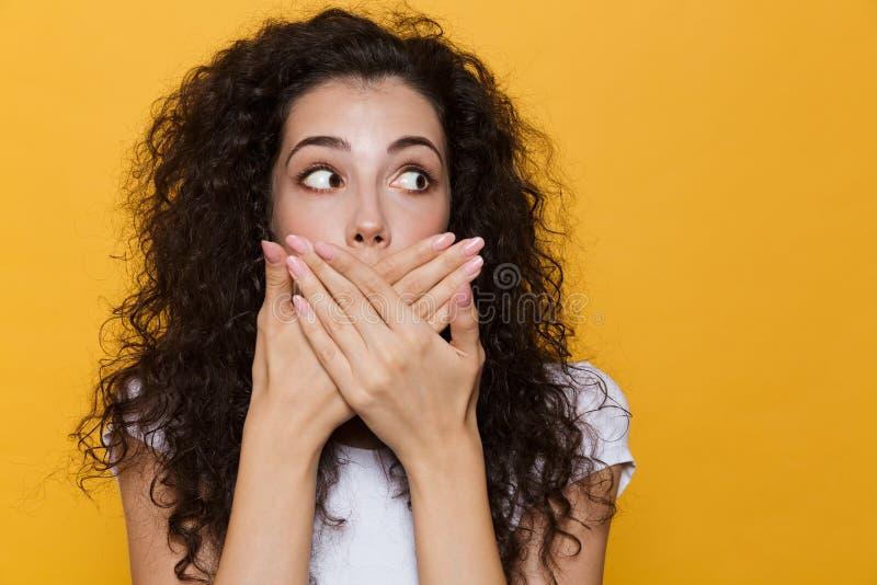 Imagen de la mujer asustada o chocada 20s con el pelo rizado que sonríe y fotos de archivo