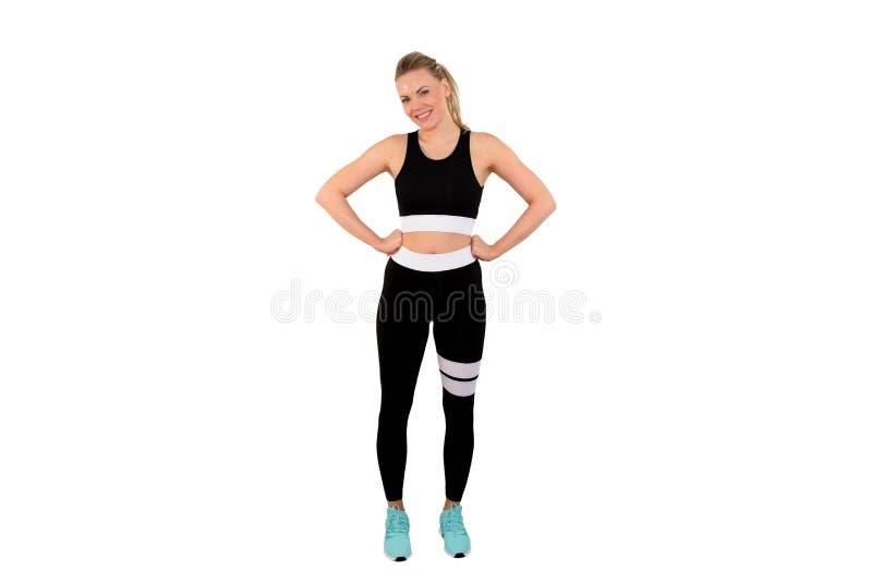 Imagen de la mujer atlética hermosa en la presentación de la ropa de deportes aislada en el fondo blanco - Imagen imagen de archivo