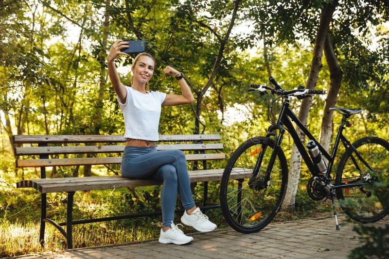 Imagen de la mujer atlética que se sienta en banco en parque con la bicicleta, y tomando la foto del selfie en el teléfono celula imagen de archivo libre de regalías