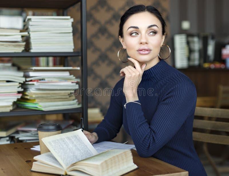 Imagen de la mujer bonita joven que se sienta en la tabla en café y libro de lectura imagen de archivo