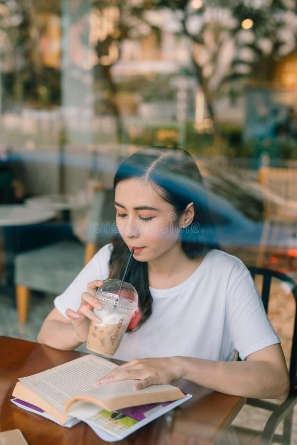 Imagen de la mujer bonita joven que se sienta en la tabla en caf? y libro de lectura fotografía de archivo libre de regalías