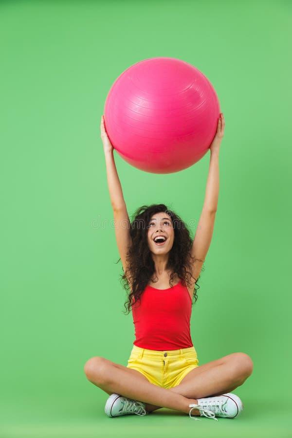 Imagen de la mujer bonita que se sienta en piso con la bola de la aptitud durante aeróbicos contra la pared verde fotografía de archivo