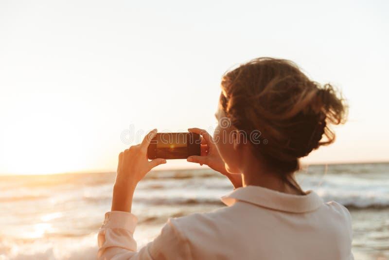 Imagen de la mujer caucásica 20s que toma la foto en smartphone, mientras que camina por la playa foto de archivo