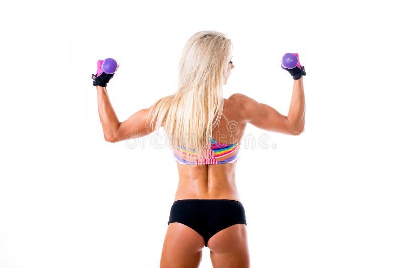 Imagen de la mujer deportiva joven que muestra su bíceps fotos de archivo