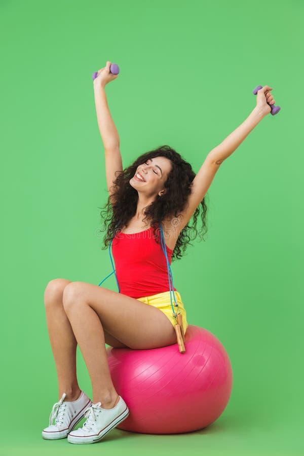 Imagen de la mujer deportiva que se sienta en bola de la aptitud durante aeróbicos contra la pared verde fotos de archivo
