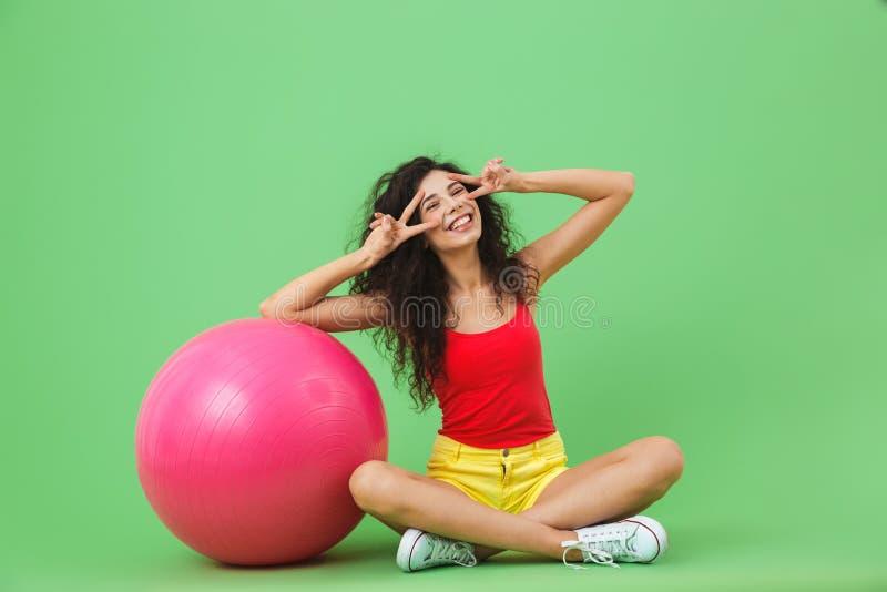 Imagen de la mujer enérgica que se sienta en piso con la bola de la aptitud durante aeróbicos contra la pared verde imagen de archivo