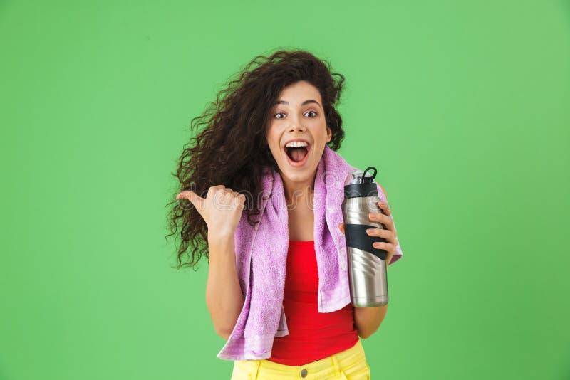 Imagen de la mujer encantada 20s en agua que disfruta y potable de la ropa de deportes después de entrenar fotografía de archivo