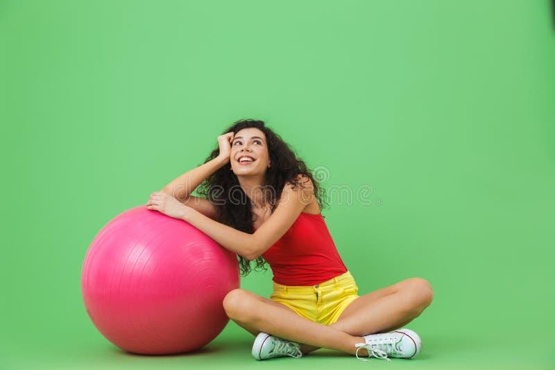 Imagen de la mujer hermosa que se sienta en piso con la bola de la aptitud durante aeróbicos contra la pared verde imágenes de archivo libres de regalías