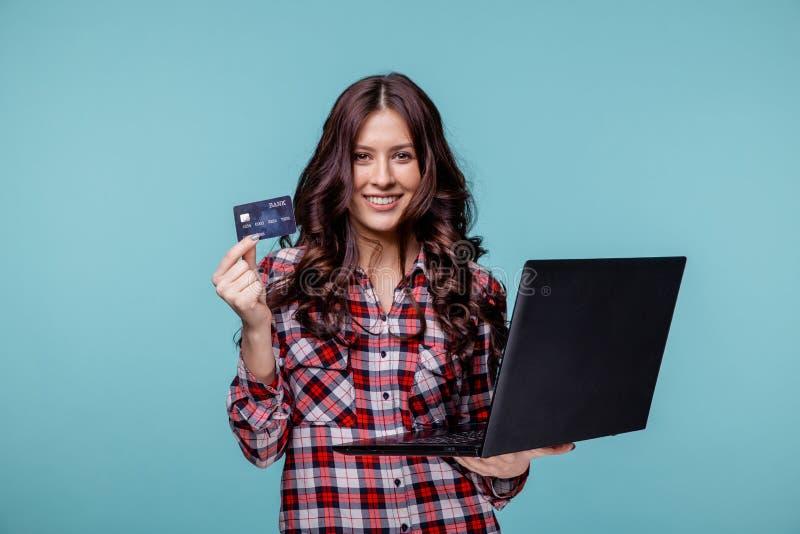 Imagen de la mujer joven agradable que sostiene el laltop negro y la tarjeta de crédito púrpura imagen de archivo