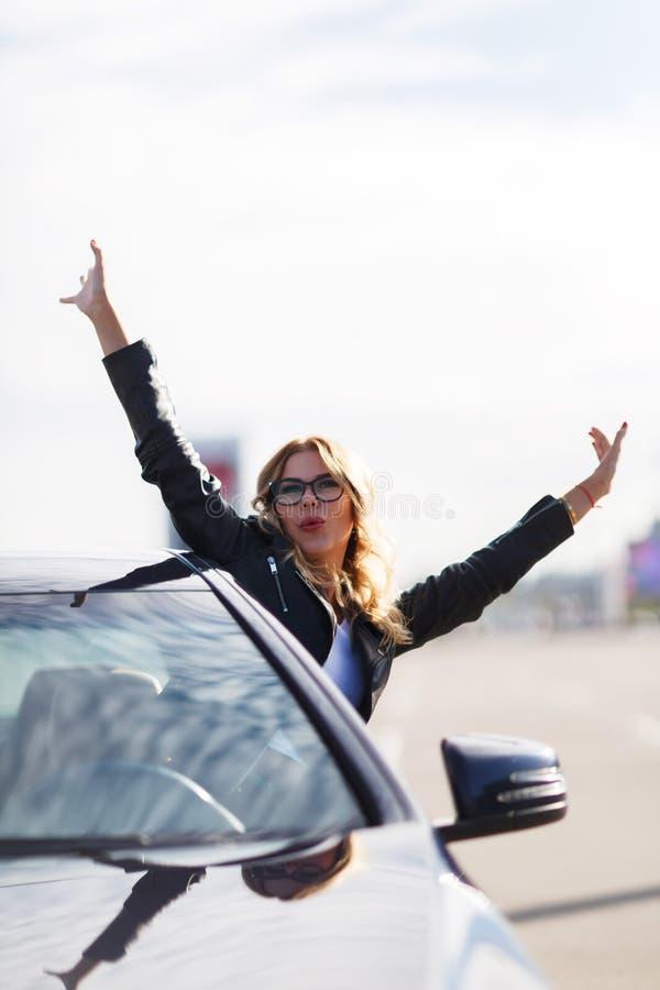 Imagen de la mujer joven con los vidrios haciendo estallar fuera del coche negro foto de archivo libre de regalías