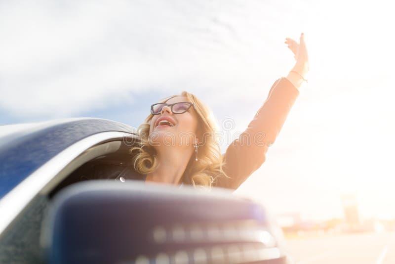 Imagen de la mujer joven con los vidrios haciendo estallar fuera del coche negro foto de archivo